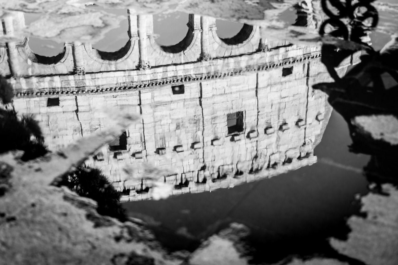 Reflectie van het Colosseum in een plas water